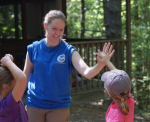 Gina giving a high five to a young camper at Camp Thoreau.